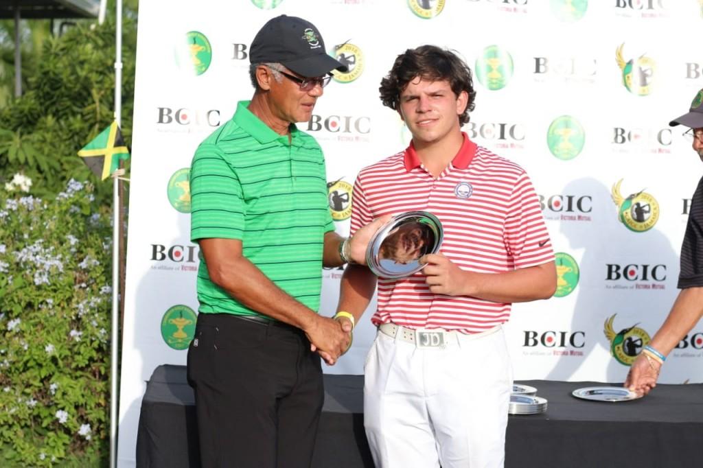 Juan Cayro Delgado (Yayo) premiado como el mejor segundo lugar en la categoría 18 o menos por el señor Peter Chin, presidente de la Asociación de Golf de Jamaica.